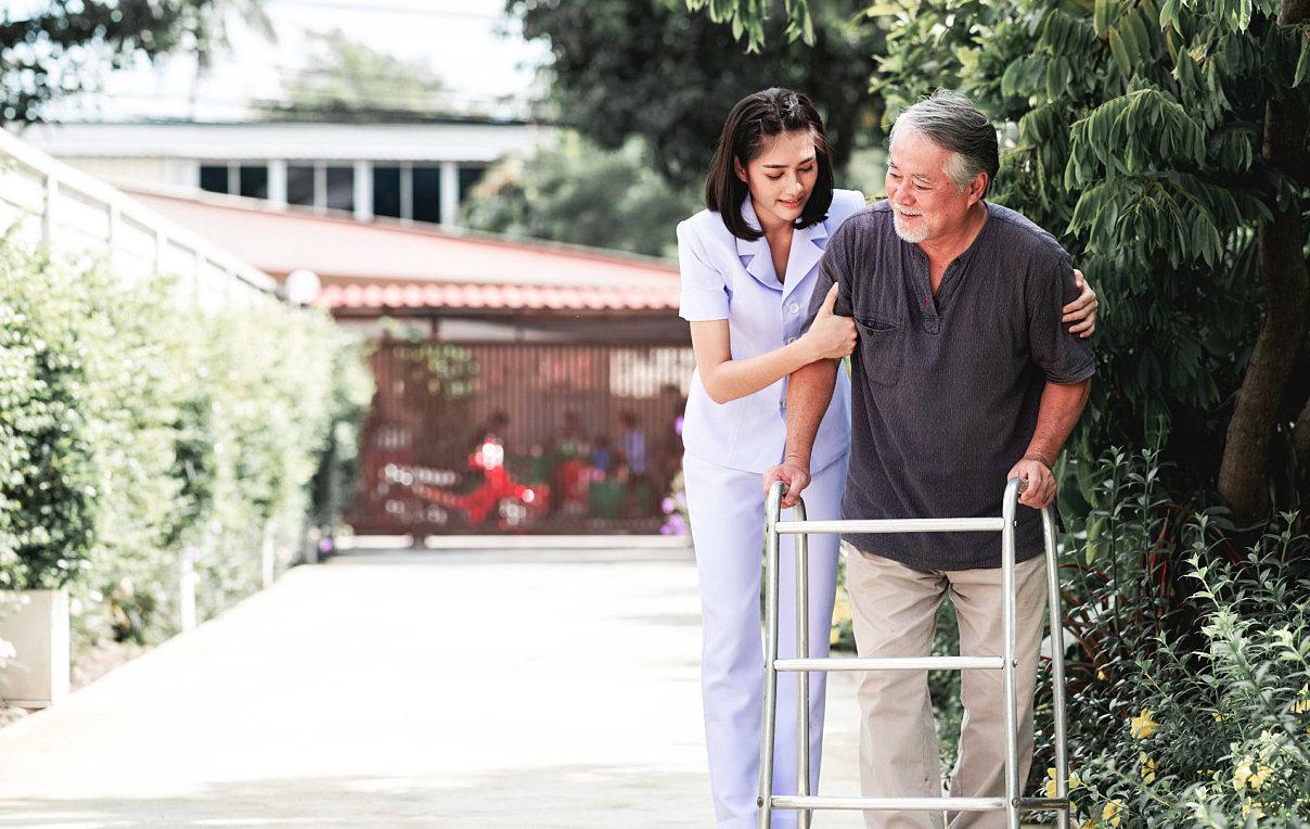 caregiver helping senior man walkt