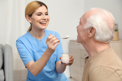 nurse feeding elderly man with yogurt