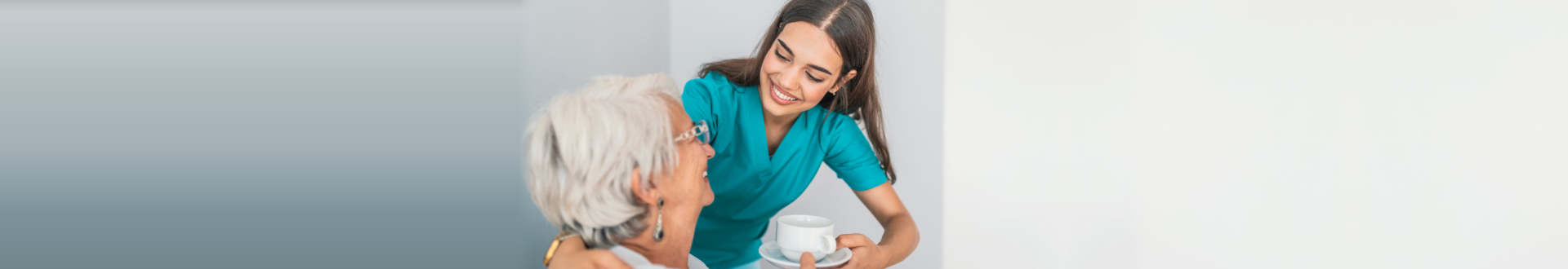 nurse giving cup of coffee to senior woman