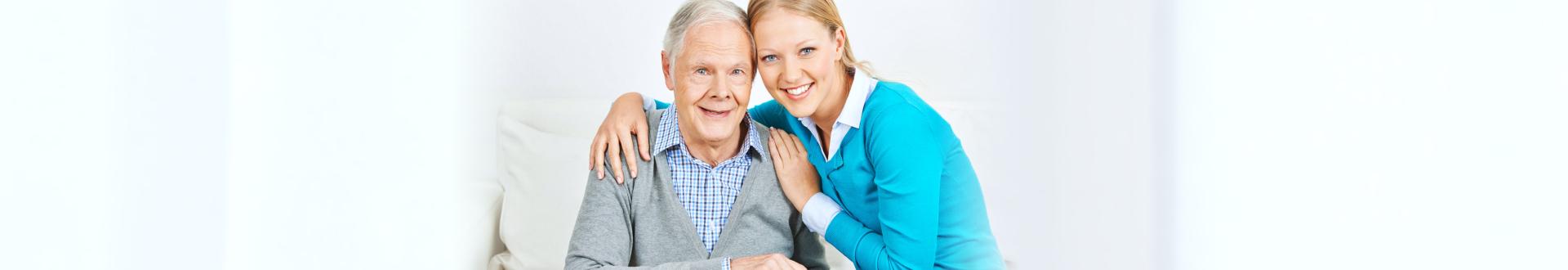 caregiver hugging senior man